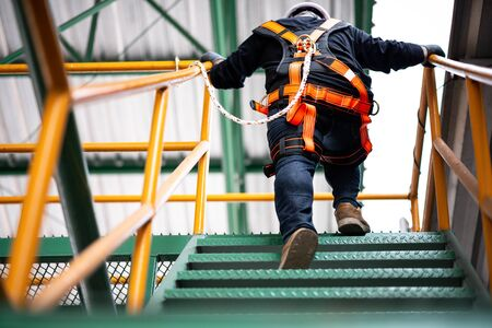 Construction worker wearing safety harness and safety line working at high place Stockfoto