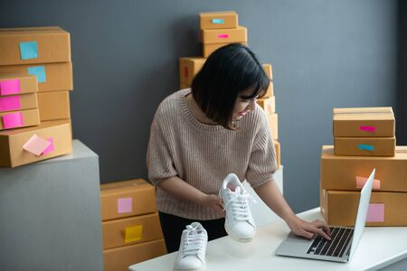 asian smiling girl using smartphone to shoot white sneaker posted for sale on the internet.startup small business owner working with tablet at workplace.happy owner & seller check product to customer