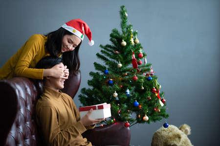 Asian women gaving Christmas gift box to boy friend.Merry Christmas and happy new year Standard-Bild