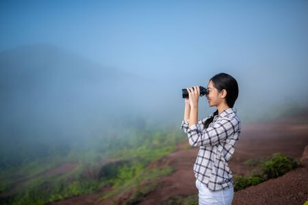 Young asian traveler looking through binoculars mountain background