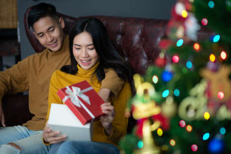 Man gaving Christmas gift box to girl friend.Merry Christmas and happy new year
