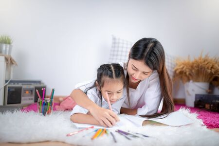 mother teach her daughter to learn how to drawing