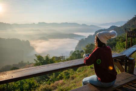 Asian traveler enjoying sunrise on Mist mountain. travel in Mae Hong Son ,Thailand
