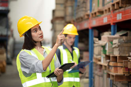 Warehouse worker checking packages on shelf in a large store