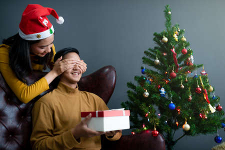 Asian women gaving Christmas gift box to her boy friend.Merry Christmas and happy new year