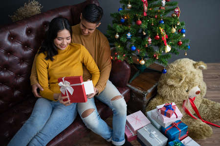 Asian man gaving Christmas gift box to his girl friend.Merry Christmas and happy new year