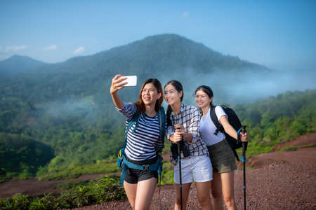 Group of asian woman hiker taking photo with smart phone at mountain peak