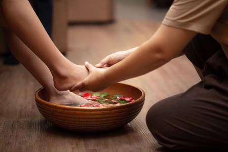 woman feet dipped in water with petals in a wooden bowl. Beautiful female feet at spa salon on pedicure procedure. Banque d'images