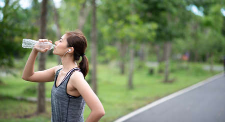 young asian woman runner doing drinking water. she athlete running at garden . sport , healthy Banque d'images