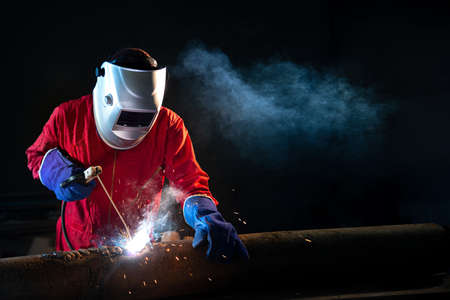 Industrial Worker welding on the pipeline construction at the factory welding