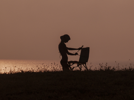 Woman artist at his easel with sunset on the beach