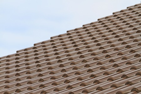 roofing system: plastic tiles on new home construction, the roof of the dwelling and the sky