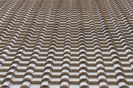 tile cladding: plastic tiles on new home construction, the roof of the dwelling, parallel lines