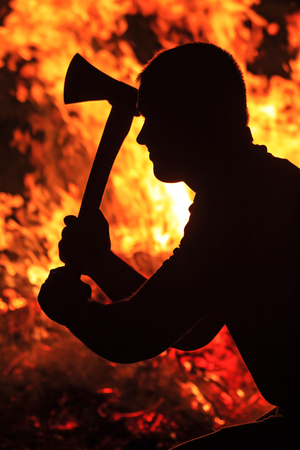 strife: man with an ax in his hands, silhouette, fire, flame, protests, terrorism, war, strife