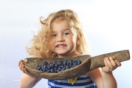 raspberry dress: The little girl holds a berry blueberries in hand, happiness, family, child, crop,smile,funny