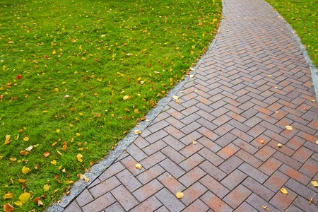 Autumn path with fallen leaves, walk gloomy day, paving slabs, green lawn
