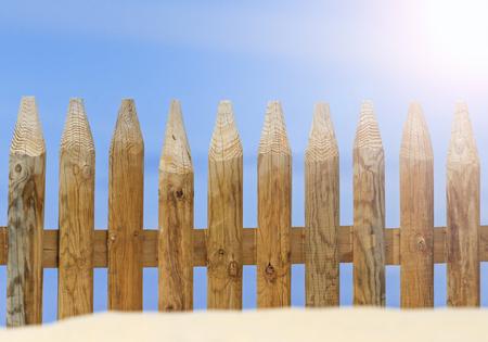 Wooden Fence buried in sand with sunny hotspot,city beach, sea, ocean, coastline Stock Photo