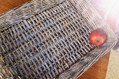 bigotry: lonely apple lying on the bottom woven box,last residue fruit basket, vintage