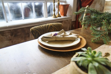 manners: plates of gold on the old oak table in the interior,retro style, vintage, aristocratic manners
