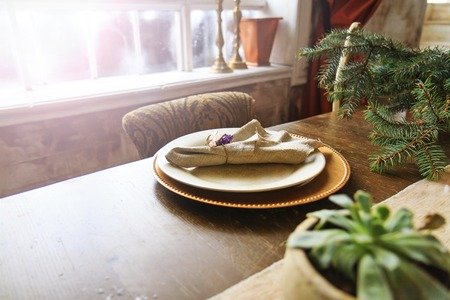 manners: plates of gold on the old oak table in the interior with sunny hotspot,retro style, vintage, aristocratic manners Stock Photo