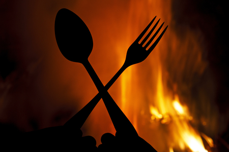 sharply: fork and spoon on a background of fire,silhouettes, hell kitchen, a creative restaurant Stock Photo