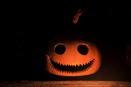 pumpkin head with a terrible smile in the dark Stock Photo