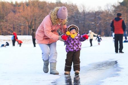 Mom and daughter slip on a skating rink among the lake