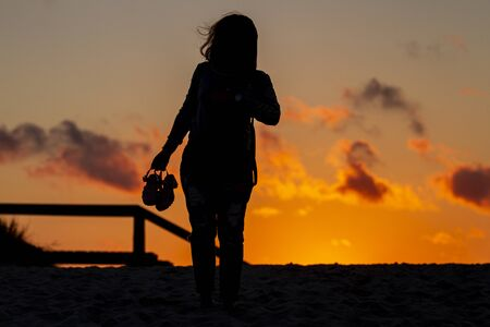 silhouette of girls with sandals at sunset