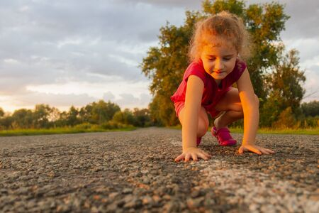 little girl at sunset lays down on warm stones Imagens