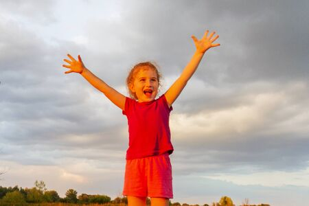 Free little girl with open arms at sunset
