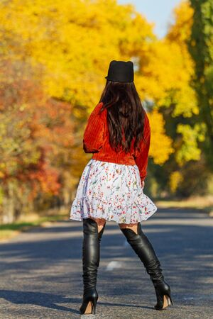 girl in high boots stands on the autumn road, exclusive