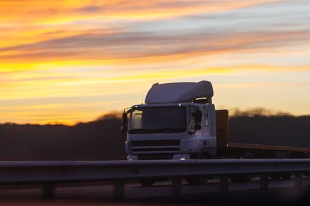 truck rides at dusk amid beautiful sunset