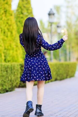 girl in a beautiful dress is walking in the spring park, spring flowering