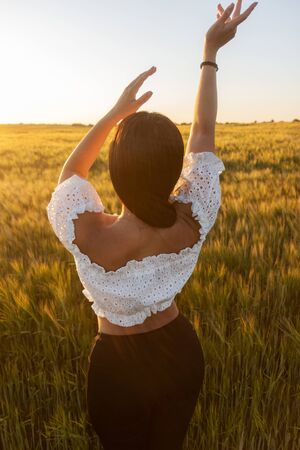 girl in a white top at sunset in a cereal field Standard-Bild