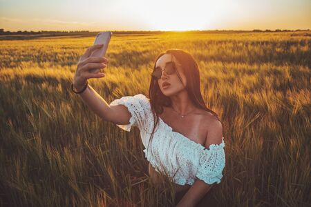 beautiful girl takes a selfie in a rye field at sunset