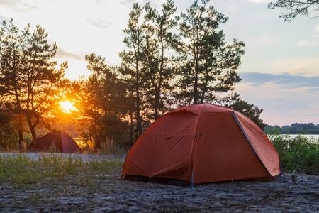 tents stand at sunrise on the river bank, summer rest Standard-Bild