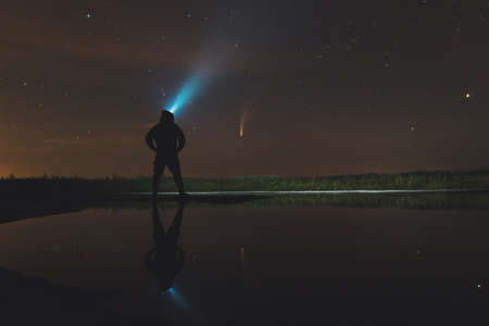 guy in the hood shines a lantern up and looks at the comet Neowise Standard-Bild