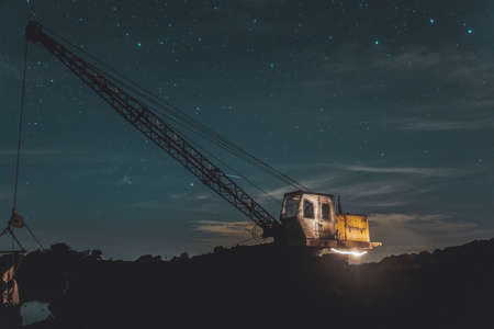excavator stands on the river bank on a starry night