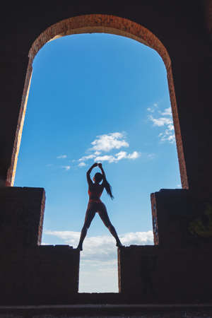 girl stands in a huge arch with her hands raised up