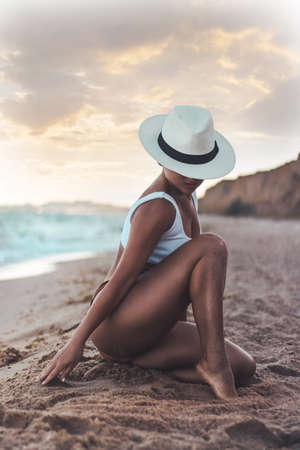 beautiful tanned girl by the sea in a big white hat