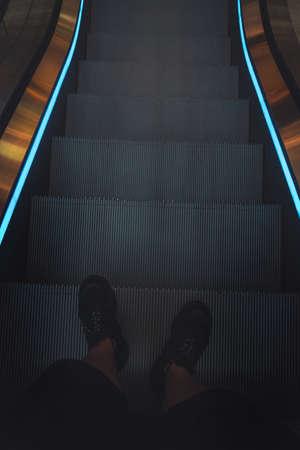 legs of a man in black sneakers on an escalator