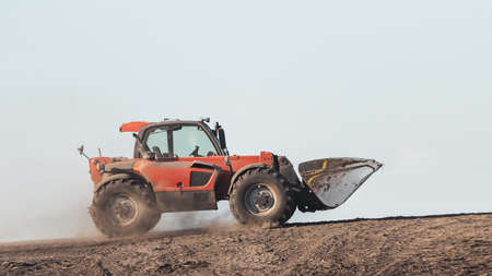 car with a bucket goes uphill through the dust Reklamní fotografie