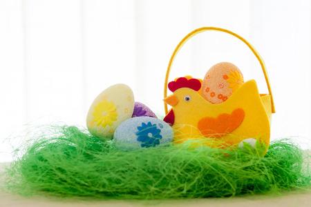 Huevos decorativos en la hierba verde. Cesta de pollo. Conceptos Pascua, huevos, hecho a mano Foto de archivo