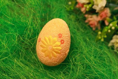 Huevo decorativo sobre la hierba verde. Conceptos Pascua, huevos, hechos a mano