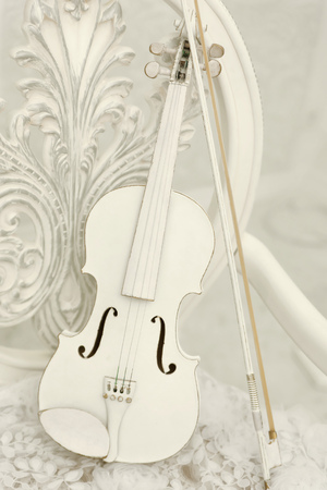 An old white violin of vintage style. Stringed musical instrument on a white forged chair Stock Photo