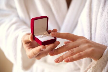 Marriage proposal. The hand holds a red gift box with a gold ring. Sentence. The best day. Gives a ring. A touch of hands. Engagement. Closeup