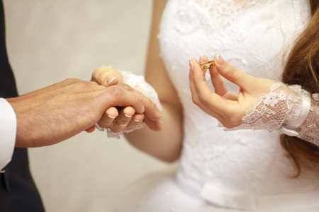 Wedding day. Ceremony. Wedding hands with rings. The bride's hand wears an engagement ring on the finger of the groom. Close up