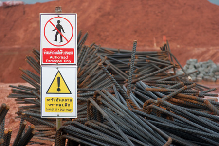 reinforcing bar: warning sign at construction site and Steel rods Stock Photo