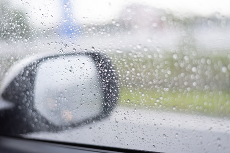 Visibility is not clear in the car mirror due to raining, rain drops on the car glass