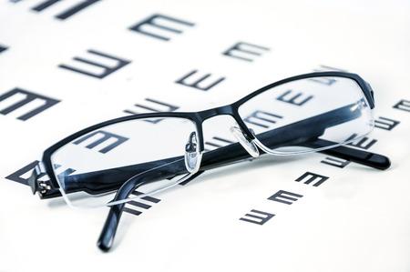sight chart: Lentes en una carta de prueba de la vista del ojo Foto de archivo